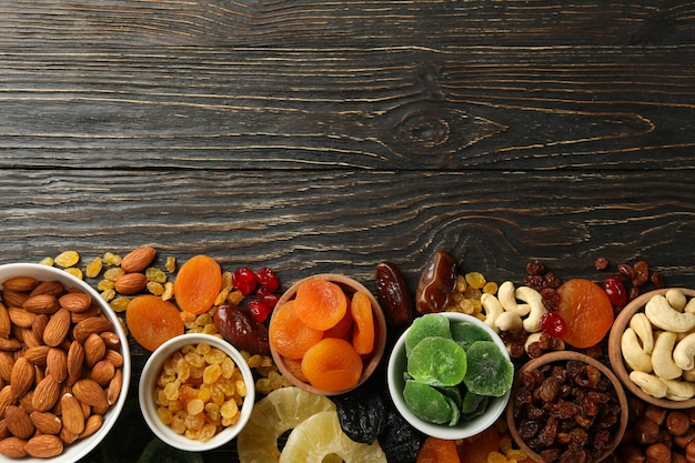 Bowls with dried fruits and nuts on wooden