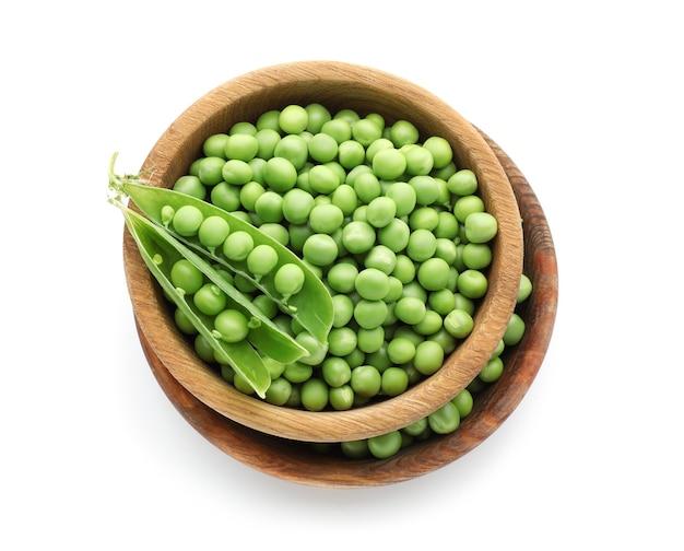 Миски со свежим зеленым горошком на белой поверхности