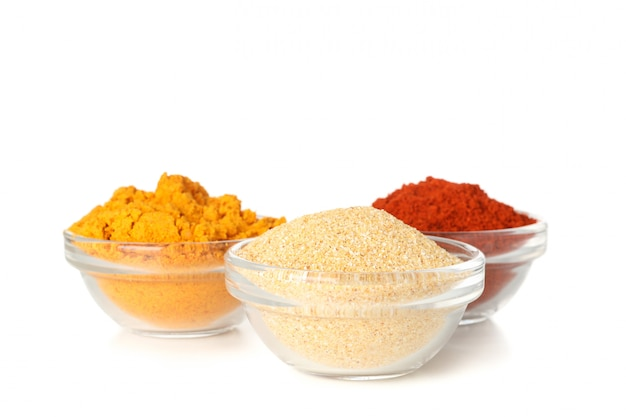 Bowls with garlic, curry and red pepper powder isolated on white