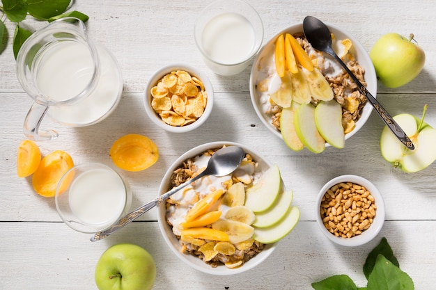 Bowls with granola, fruit, yogurt and two glasses with milk on a white wooden. healthy breakfast cereal