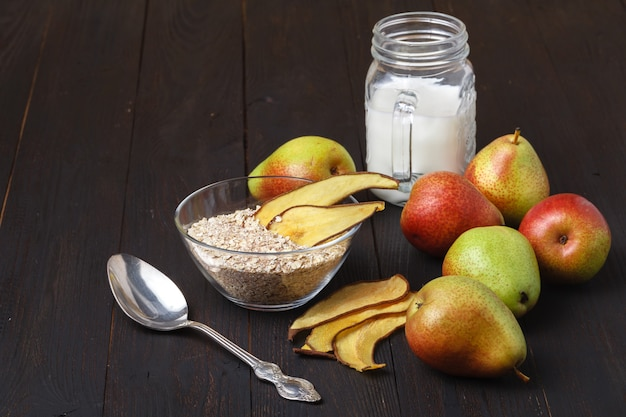 Bowls with healthy breakfast and pears on a wooden table.