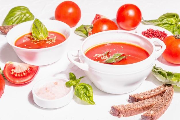 Чаши с домашним томатным супом. спелые овощи, свежие листья базилика, хлебные палочки, ароматные специи. модный жесткий свет, темная тень. белый фон шпатлевки, плоская планировка