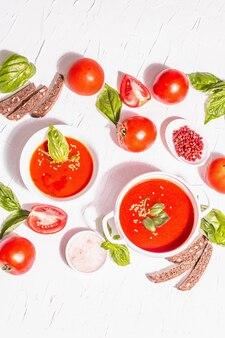 Чаши с домашним томатным супом. спелые овощи, свежие листья базилика, хлебные палочки, ароматные специи. модный жесткий свет, темная тень. белый фон шпатлевки, вид сверху