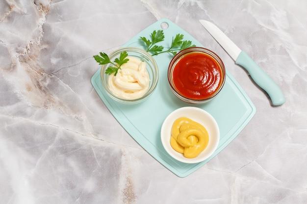 식탁에 케첩, 겨자, 치즈 소스가 있는 그릇.