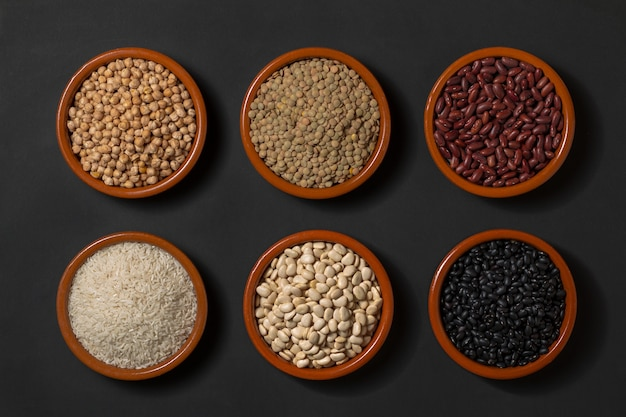 Bowls with legumes. lentils, chickpeas, rice and different kinds of beans.