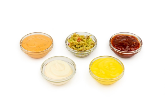 Bowls with mexican cuisine sauces, guacamole, chili, cheese, paprika on a white plate.