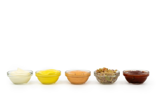 Bowls with mexican cuisine sauces, guacamole, chili, raw, paprika on white background.