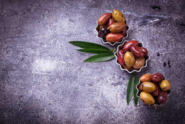 Bowls with mix of pickled mediterranean olives on concrete background.  selective focus