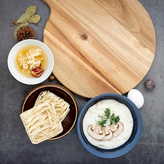 Bowls with noodles and mushroom soup on a grey background with a wooden support