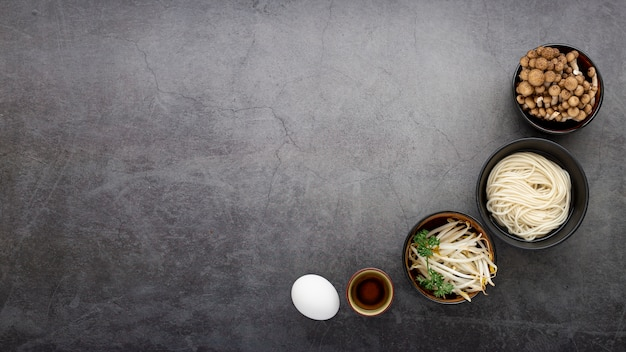 Bowls with noodles and mushrooms on a grey background