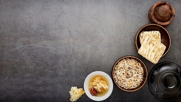 Bowls with noodles and musli on a grey background