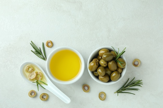 Bowls with olives and oil on white textured surface