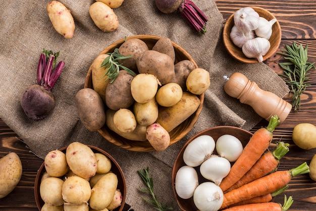 Ciotole con patate carota e aglio sul tavolo