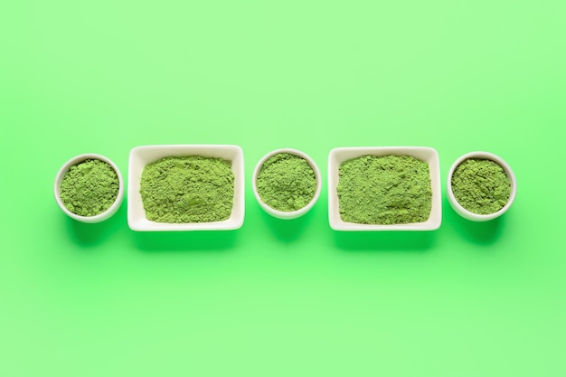 Bowls with powdered matcha tea on color background