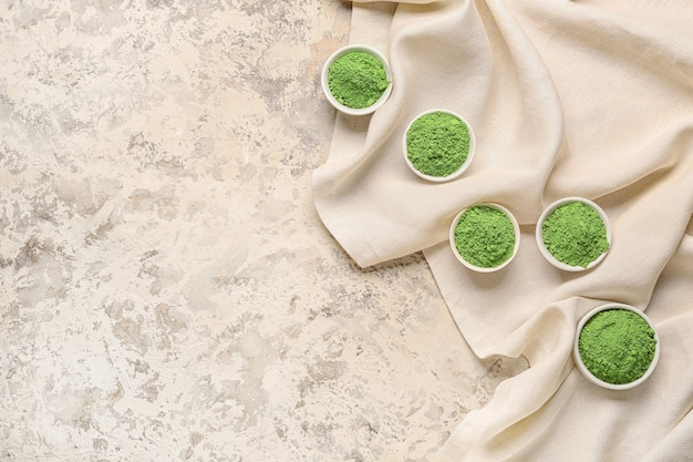 Bowls with powdered matcha tea on light background