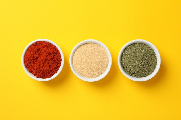 Bowls with red pepper, garlic and dill powder on yellow background, top view