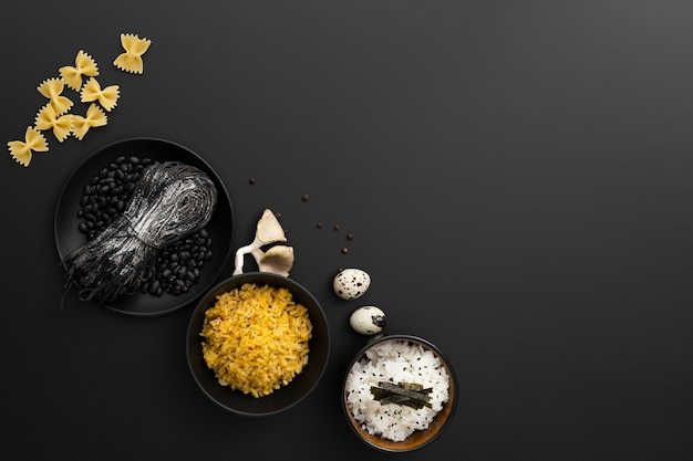 Bowls with rice and pasta on a dark background