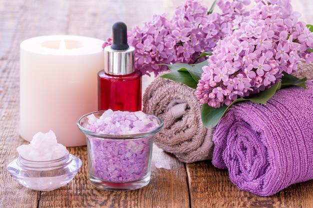 바다 소금이 든 그릇, 불타는 초, 아로마 오일이 든 빨간 병, 수제 비누, 라일락 꽃, 나무 판자에 욕실 절차를 위한 수건. 스파 제품 및 액세서리