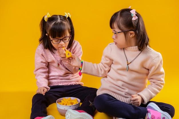Миски с закусками. приятная темноволосая девушка, добрая и милая, предлагает сестре чипсы