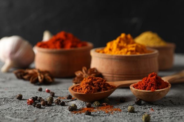 Bowls with spices and ingredients on grey