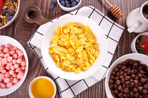 Bowls with strawberry, chocolate sweet corn balls, muesli and corn flakes with berries. delicious and healthy breakfast cereal. top view.