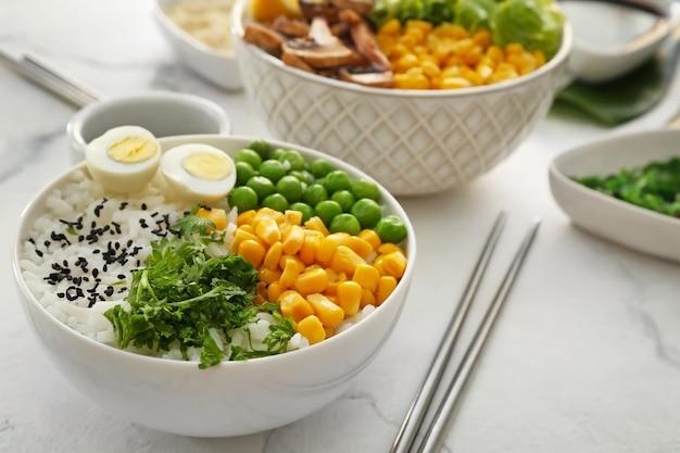 Миски с вкусным рисом и овощами на столе