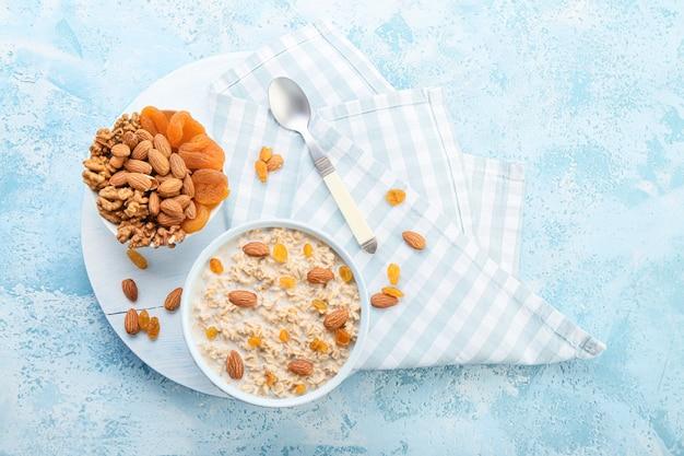 Чаши с вкусной сладкой овсянкой, сухим абрикосом и орехами на цвете