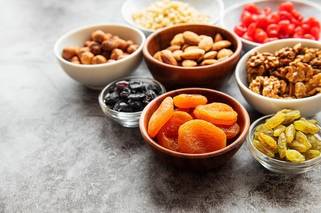 회색 콘크리트 표면에 다양한 말린 과일과 견과류와 그릇