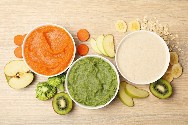 Bowls with vegetable puree on wooden background. baby food