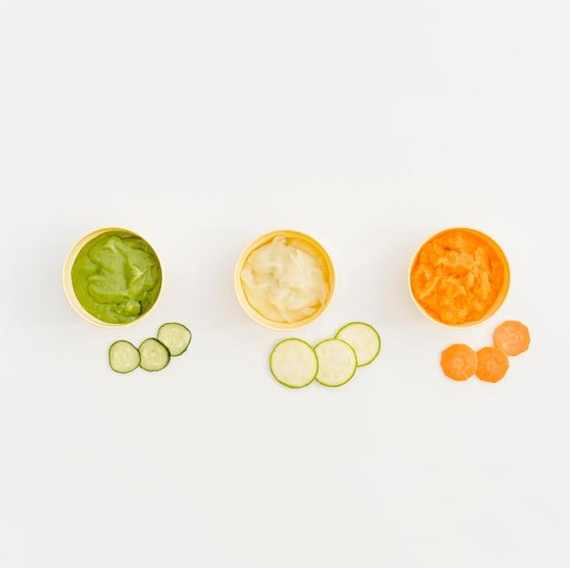 Миски с овощным пюре для ребенка на столе