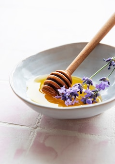 Bowlwith honey and fresh lavender flowers on a pink tile background