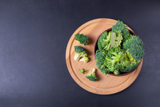 木製キッチンプレートと黒の背景に素朴なbownlで新鮮なカット緑ブロッコリー。コピースペースでフラットレイアウト