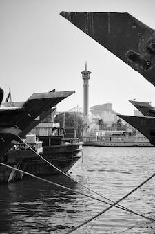 아랍에미리트(uae) 두바이 크릭(dubai creek)을 가로질러 데이라(deira)에 있는 아랍 선박의 활과 개런드 모스크(garand mosque)의 첨탑