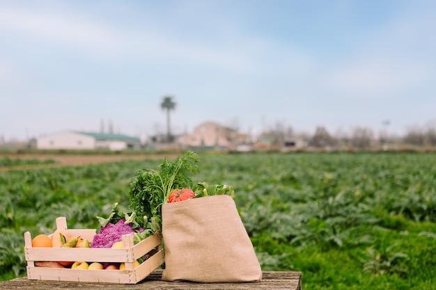 작물 분야에서 야채와 함께 상자와 가방