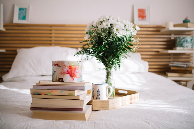 Box on books near tray with bouquet