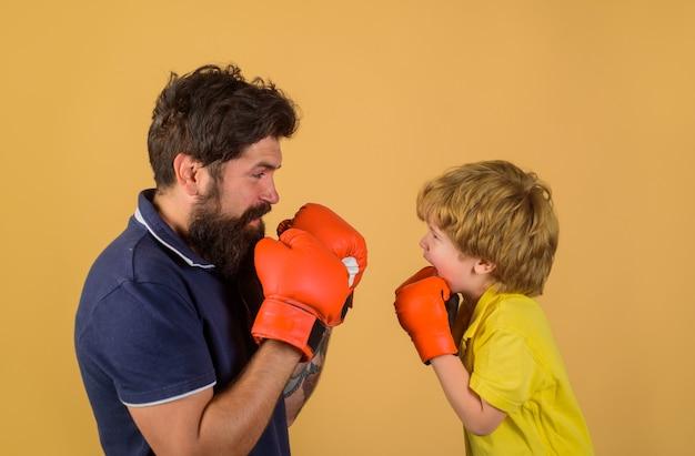 Коробка. боксер. готов к спаррингу. маленький ребенок боксирует с тренером. спортивный образ жизни. тренируемся вместе. семейная тренировка.