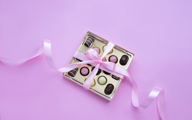 Box of chocolate pralines with pink bow on pink background