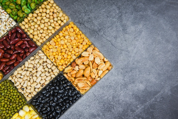 Box of different whole grains beans and legumes seeds lentils and nuts colorful snack background top view - collage various beans mix peas agriculture of natural healthy food for cooking ingredients