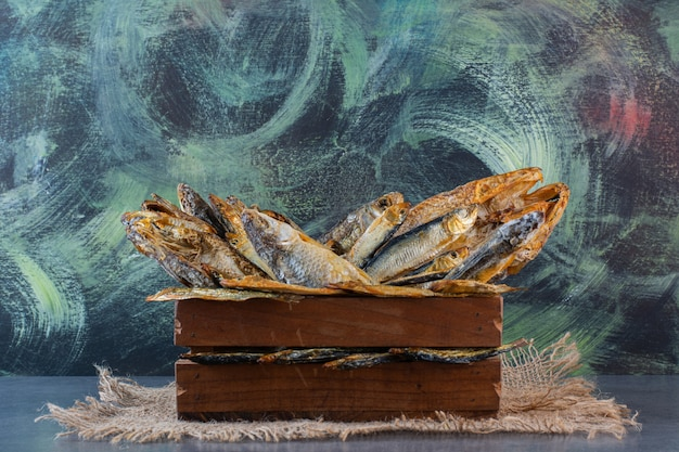 Box of dried fish on a burlap napkin on the marble surface