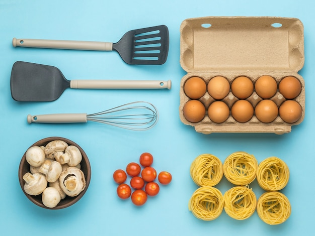 A box of eggs, a bowl of mushrooms, pasta, tomatoes, and cooking utensils. ingredients for making pasta.