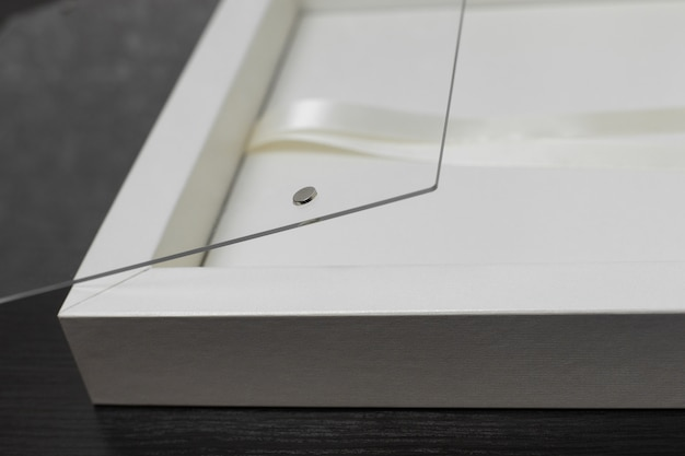Коробка для свадебного фотоальбома на деревянных фоне. стильная коробка для семейной фотокниги с copyspace. подарочная коробка с лентой со стеклянной крышкой.