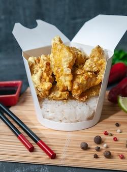 냄비 상자. 카레와 코코넛 크림 소스에 쌀과 농어 필레.