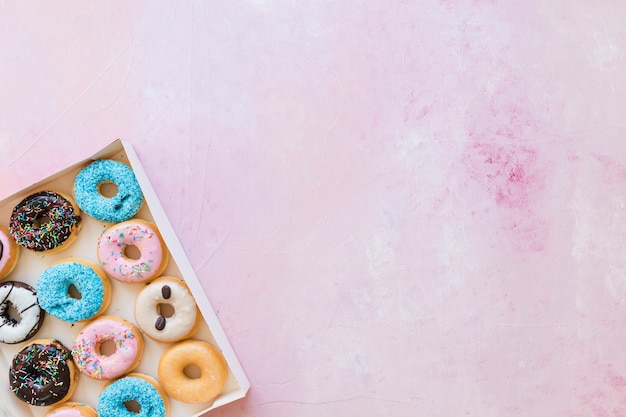 Box of fresh donuts on pink background