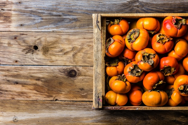 Box of fresh fruits persimmon kaki on wooden background. copy space