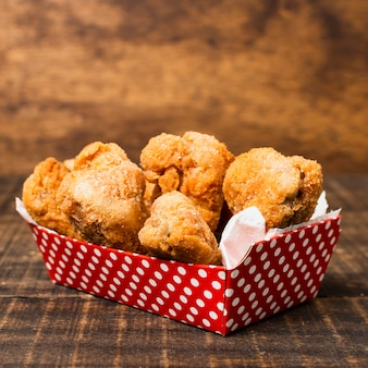 Box of fried chicken on wooden table