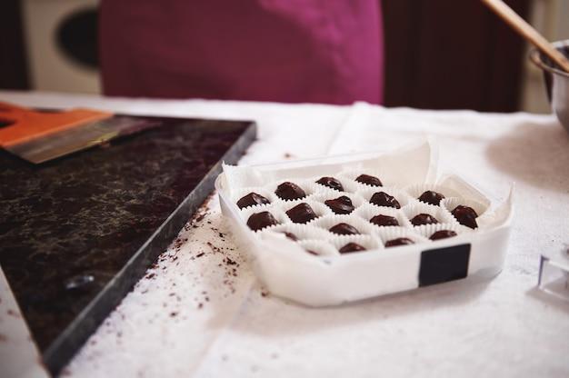 Коробка с шоколадными трюфелями и конфетами ручной работы на белой скатерти рядом с мраморной поверхностью со скребком на ней