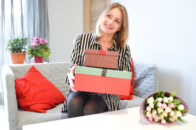 女性へのボックスギフト。女の子はギフトボックスを開きます。驚きの喜び。花を持つ女性。