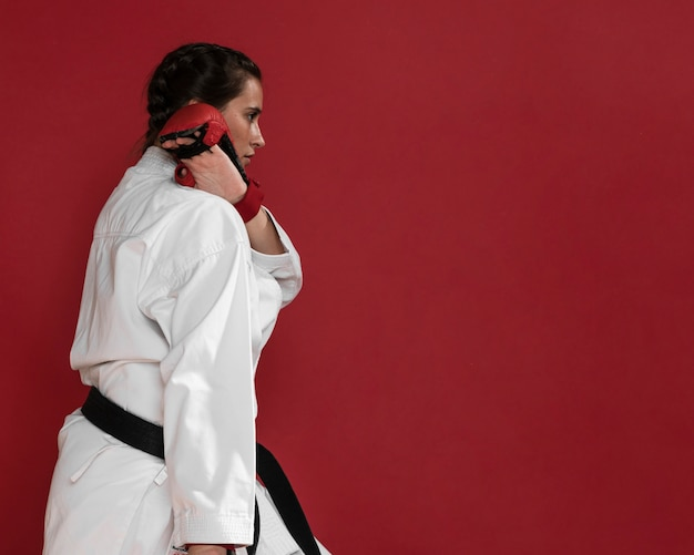 Box gloves on red background and woman fighter