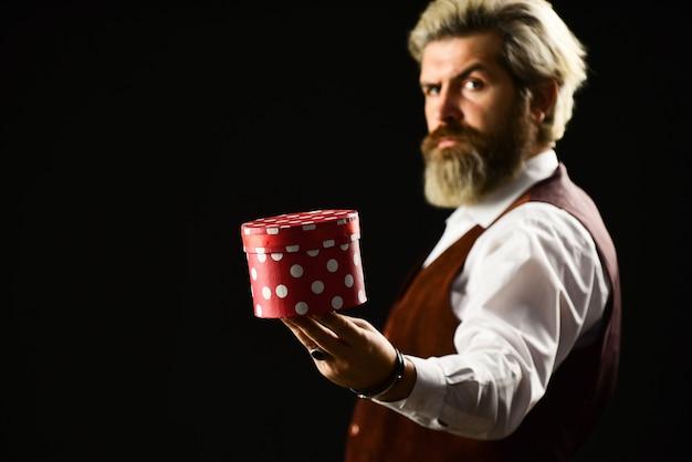 박스 홀리데이 패키지. 특별한 날. 독특하고 독특합니다. 소중한 제품을 전해드립니다. 완벽한 선물. 온라인 쇼핑. 검은 금요일. 잘생긴 남자 선물 상자입니다. 성숙한 수염 난 힙스터가 선물 상자를 들고 있습니다.