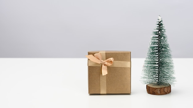 Box is wrapped in brown paper and a decorative christmas tree on a white table. festive background, copy space